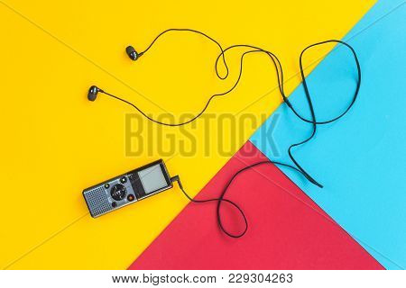 Black voice recorder with headphones on a combined yellow, blue and red background. Journalism conce