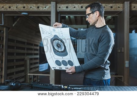 Side View Of Shooter Looking At Used Target After Shooting In Gallery