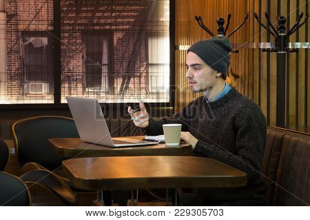 Man Speaks Online In Cafe Via Internet Messenger On Computer. Young Male Person Explains Something,