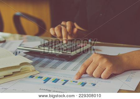 Man Hand Using A Financial Calculator With Writing Make Note And Financial Data Analyzing On Desk At