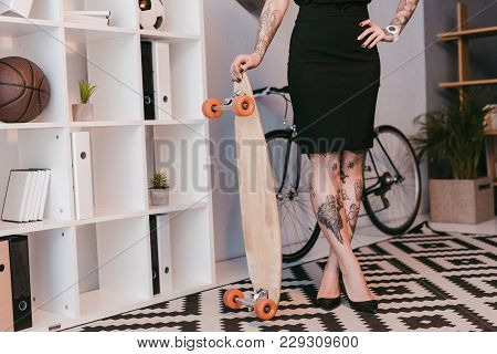 Partial View Of Young Businesswoman Standing With Skateboard In Office