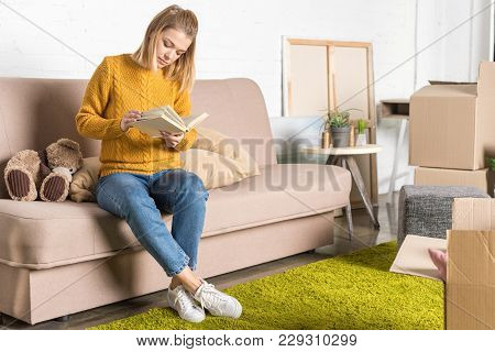 Attractive Young Woman Sitting On Sofa And Reading Book During Relocation