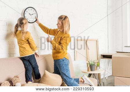 Mother And Daughter Hanging Clock On Wall During Relocation