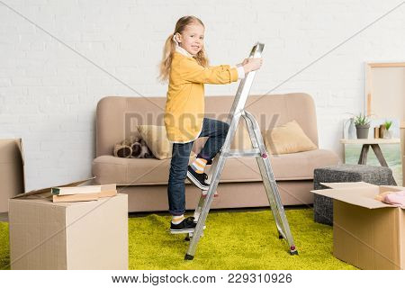 Cute Little Child Standing On Ladder And Smiling At Camera During Relocation