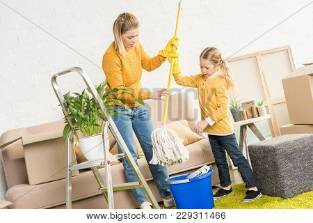 Mother And Daughter Holding Mop And Cleaning Room After Relocation