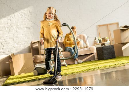 Smiling Little Child Cleaning Room With Vacuum Cleaner While Mother Reading Book On Sofa After Reloc