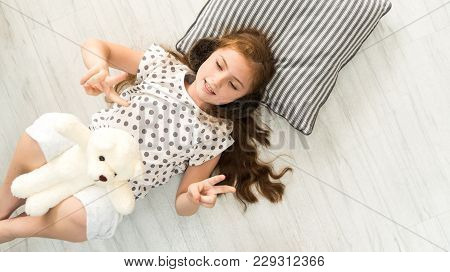 Top View Of Happiness Caucasian Girl Kid  And Black Boy Smile Have Fun Are Lying Down  To Playing Wi