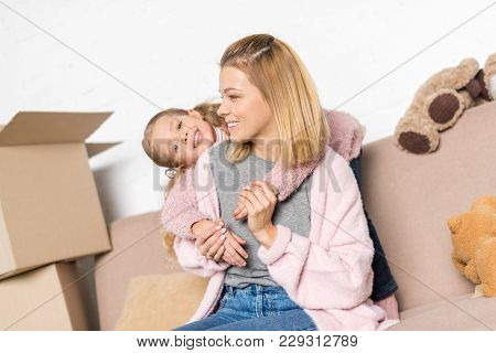 Happy Mother And Daughter Hugging While Sitting On Sofa During Relocation