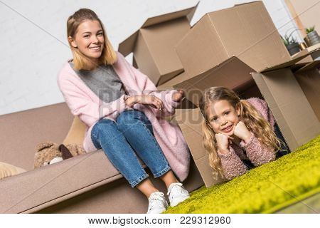 Happy Mother And Daughter Having Fun With Cardboard Boxes While Relocating