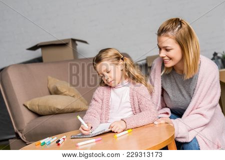 Happy Mother Looking At Daughter Drawing With Felt Tip Pens At Table