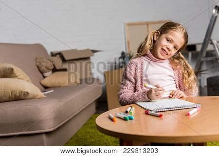 Cute Little Child Drawing With Felt Tip Pens And Smiling At Camera At Home