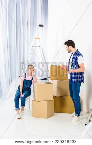 Boyfriend Showing Shrug Gesture And Looking At Girlfriend Sitting On Boxes