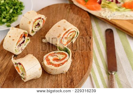 Rolls Of Thin Pancakes With Smoked Salmon, Cream Cheese, Chives And Lettuce.