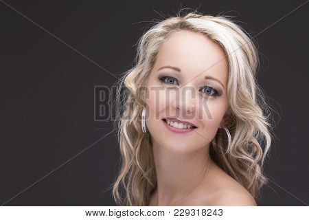 Beautiful Blond Woman In Curly Hair And Black Top On A Grey Background