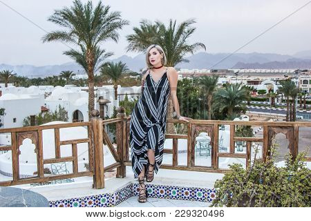 Beautiful In Dress Looking At Camera While Leaning At Wooden Railing At Resort In Egypt