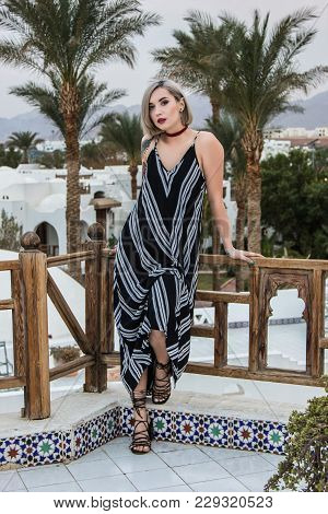 Attractive Young Woman In Dress Looking At Camera While Leaning At Wooden Railing At Resort In Egypt