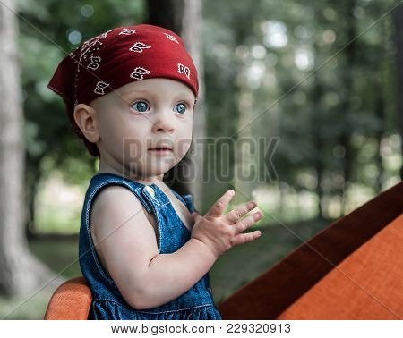 A Portrait Of A Cute Little Baby Girl In A Blue Jeans Dress And A Red Bandana. The Enfant Has Beauti