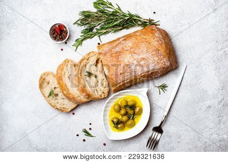 Italian Ciabatta Bread Cut In Slices With Herbs And Olives.