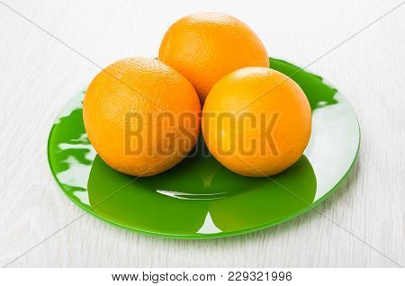 Ripe Oranges In Green Plate On Wooden Table