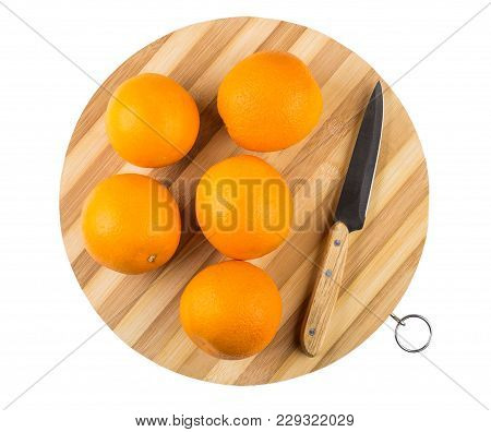 Ripe Oranges And Kitchen Knife On Round Striped Cutting Board Isolated On White Background. Top View