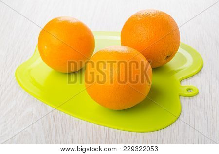 Three Oranges On Green Plastic Cutting Board On Wooden Table