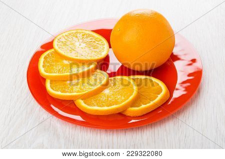 Whole Orange And Slices Of Orange In Red Plate On Wooden Table