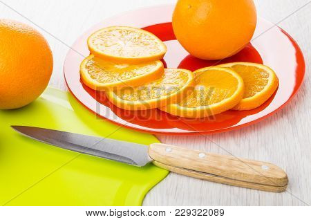 Whole Orange And Slices Of Orange In Plate, Cutting Board And Knife On Wooden Table