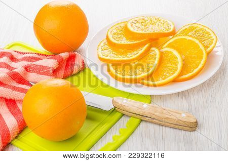 Slices Of Orange In White Plate, Whole Orange On Cutting Board, Kitchen Knife On Wooden Table