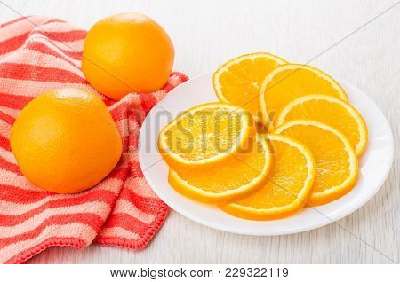 Slices Of Orange In Plate, Whole Orange On Red Napkin On Wooden Table