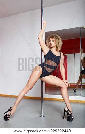 Beautiful Blond Young Woman Training On Pylon At Pole Dance Studio. Red Curatins. Copy Space.