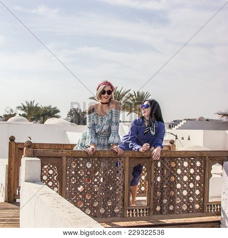 Beautiful Smiling Girls In Dresses And Sunglasses Leaning At Wooden Railing At Resort In Egypt