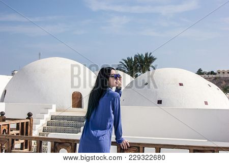 Attractive Girl In Dress And Sunglasses Leaning At Wooden Railing And Looking At Architecture In Egy