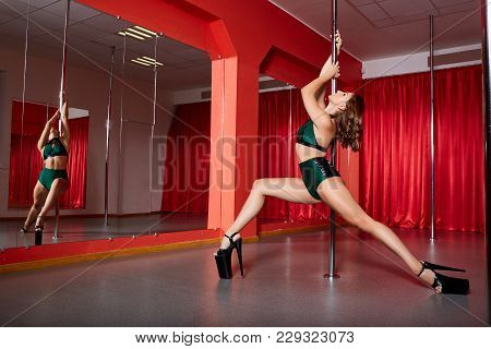 Beautiful Brunette Young Woman Training On Pylon At Pole Dance Studio. Red Curatins. Copy Space.