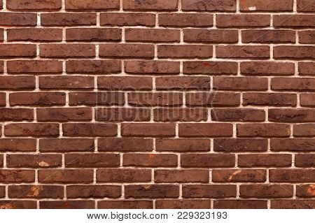 Decorative, Neat Wall Made Of Brown Ceramic Bricks, Inside. Modern Imitation Of The Old Brickwork. T