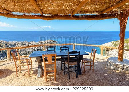 Table And Chairs In Traditional Greek Tavern With View Of Beautiful Ionian Sea. Zakynthos. Zante, Gr