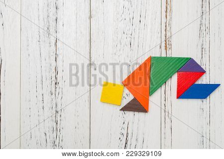Wooden Tangram Shaped Like A People Kneeling Down With Copy Space