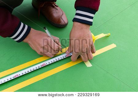 Workers Measuring And Marking The Sideline On The Floor For An Outdoor Stadium
