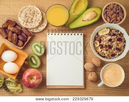 Healthy Breakfast Concept With Muesli, Avocado, Kiwi, Orange Juce, Coffee Cup And Note Book. Diet Pl