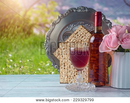 Passover Holiday Celebration Concept With Wine, Matzo, Flowers And Seder Plate Over Green Grass Back
