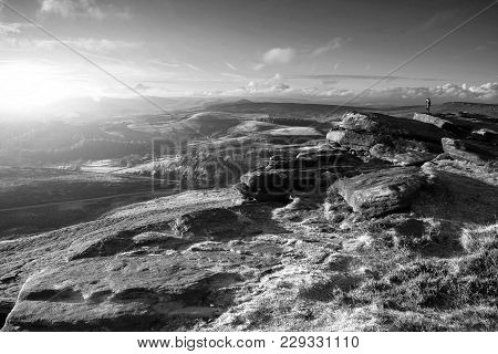 Hikers In Beautiful Black And White Peak District Landscape During Autumn Sunset