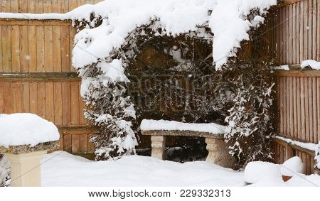Stone Bench Covered In Snow In A Country Garden