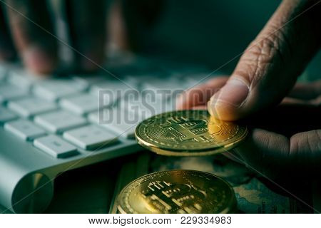 closeup of a young man having a bitcoin from a pile of bitcoins while is using a computer, with a dramatic effect