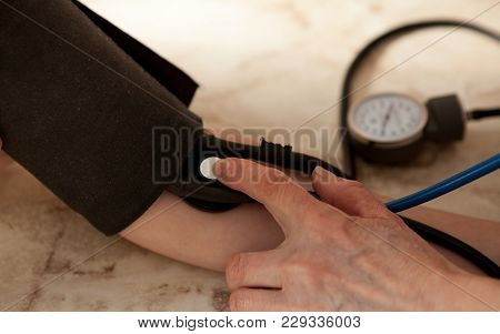 Cropped Image Of Male Doctor Checking Blood Pressure Of Patient At Table.