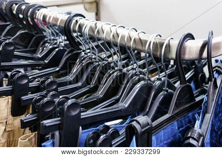 Closeup shot of row of pants and jeans on the hangers in modern clothing store