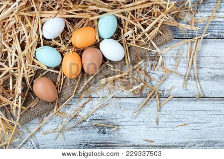 Overhead View Of Natural Raw Eggs Resting On Straw And Burlap With White Rustic Wood
