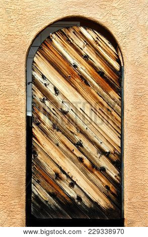 Rustic Wooden Door Fits Perfectly In The Arched Doorway Of An Adobe Home.  Boards Are Rough And Weat