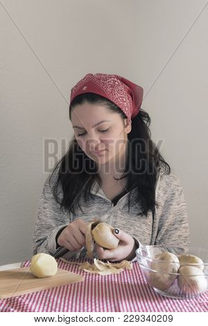Young Woman Cooking Potatoes - Young Brunette Woman Peeling Potatoes On A Table In Sunlight.