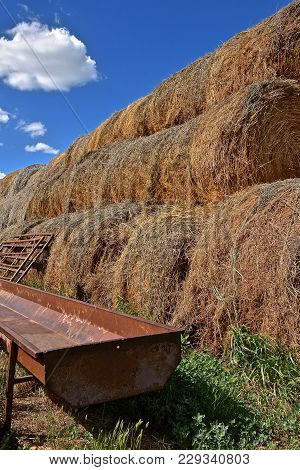 An Empty Metal Feed Bunk Is Adjacent To A Row Of Stacked Round Bales