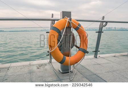 Closeup Of Tied Orange Lifebuoy, Water Background