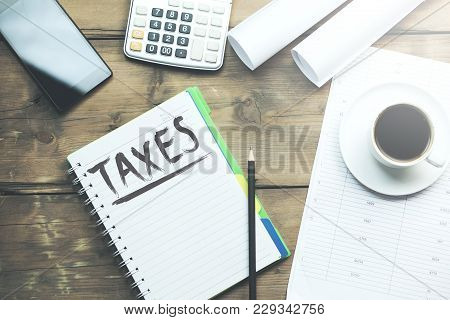 Taxes Word  On Notebook On The Wooden Table